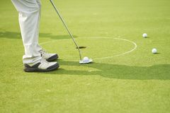 Unrecognizable mężczyzna bawić się golfowego kładzenie na zieleni Zdjęcie Royalty Free