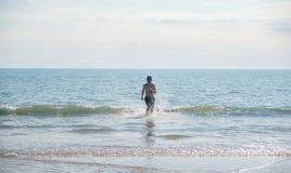 Unrecognizable mężczyzna brunetka w błękicie zwiera bieg z morza w lecie, piaskowata plaża Fotografia Stock
