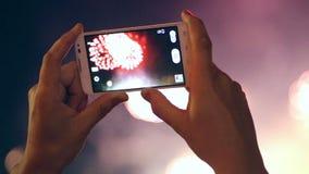 Unrecognizable mężczyzna filmuje kolorowych fajerwerki na jego telefonie komórkowym zbiory