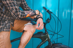 Unrecognizable mężczyzna obsiadanie Na Rowerowego Pobliskiego błękit ściany tła Dziennego stylu życia Miastowym Odpoczynkowym poj Zdjęcie Stock