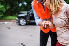 Unrecognizable mężczyzna pomaga młodej kobiety chodzić po wypadku samochodowego Obraz Stock