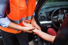 Unrecognizable mężczyzna sprawdza puls żeński kierowca po wypadku samochodowego Obrazy Stock