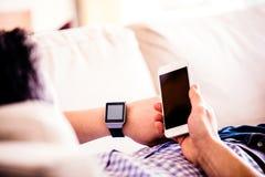 Unrecognizable mężczyzna używa smartphone i mądrze zegarek w domu fotografia stock