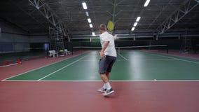 Unrecognizable męski bawić się tenis na sądzie i zbiory