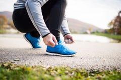 Unrecognizable młody biegacz wiąże shoelaces zdjęcia stock
