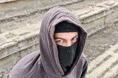 Unrecognizable młody człowiek jest ubranym czarnego balaclava obsiadanie na starym Obraz Royalty Free