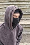 Unrecognizable młody człowiek jest ubranym czarnego balaclava obsiadanie na starym Fotografia Royalty Free