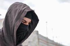 Unrecognizable młody człowiek jest ubranym czarnego balaclava obsiadanie na starym Zdjęcie Stock