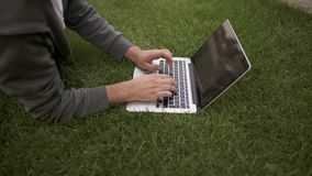 Unrecognizable młody człowiek pisać na maszynie na jego laptopu lying on the beach na gazonie, boczny widok zdjęcie wideo