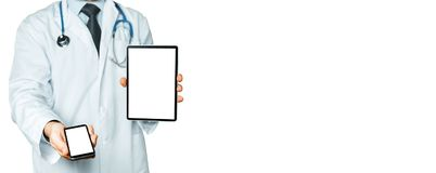 Male Doctor Holds Smartphone And Digital Tablet With Copy Space And Clipping Path For Screen stock photography