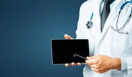 Doctor Using Digital Tablet In Consultation With Patient On Blue Background With Space royalty free stock image