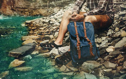 Unrecognizable Male Hiker Sits On River And Enjoys Surrounding View Exploring Adventure Hiking Concept. Unrecognizable young tourist with a backpack, stopped for Royalty Free Stock Photography