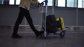 Unrecognizable male passenger with luggage trolley in the international airport. Walking in the hurry, side view