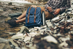 Unrecognizable Male Traveler Drink Tea Or Coffee From Thermos  Hiking Leisure Resting Concept. A young traveler in sunglasses lies on the rocks near the river Stock Photo