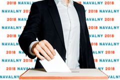 Man Putting A Ballot Into A Voting box. Democracy Election In Russia Navalny Concept. Unrecognizable male voter holds in his hand a ballot above the ballot box Stock Photography