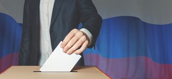Man Voter Putting Ballot Into Voting box. Democracy Freedom Concept On Flag Background. Unrecognizable male voter holds in his hand a ballot above the ballot box Stock Photography