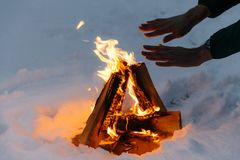 Unrecognizable male warms hands on fire in forest during cold winter, tries to warm himself, being cold spend time on cold snow an. D frosty weather. Burning royalty free stock photo