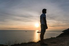 Unrecognizable man admires the sunset on a mountain with seascape. Side view. Royalty Free Stock Photos