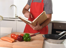 Unrecognizable man in apron at kitchen following recipe book healthy cooking. Unrecognizable man in red apron at home kitchen following recipe book preparing Royalty Free Stock Photos