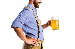 Unrecognizable man in bavarian clothes holding mug of beer Stock Photo