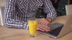 Unrecognizable man with beard computing on laptop. Male hands typing on keyboard laptop. On the wooden table glass with orange juice. Close up details stock footage
