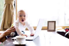 Unrecognizable man in cafe having coffee, holding his son Royalty Free Stock Image