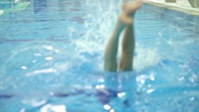 Unrecognizable man diving in the swimming pool. Slow motion close up shot. Clip stock footage