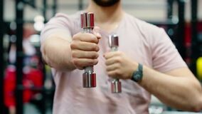 Unrecognizable man doing exercise with lightweight dumbbell in gym