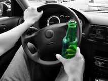 Unrecognizable man drinking and driving. Black and white. Focus Stock Images