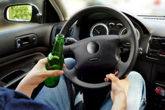 Unrecognizable man drinking and driving. Dangerous driving conce. Pt Stock Images