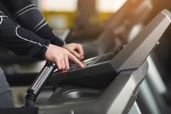 Unrecognizable man in gym running on treadmill. Unrecognizable man hands on elliptical trainer handrails in sport club. Cardio workout background, running on Stock Images