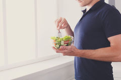 Unrecognizable man has healthy lunch, eating diet vegetable salad. Man eat healthy lunch in modern interior. Unrecognizable profile male torso in blue t-shirt Royalty Free Stock Image
