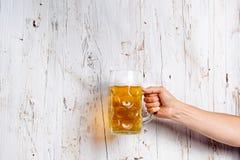 Unrecognizable man holding a beer mug, studio shot. Hand of unrecognizable men holding a beer mug. Oktoberfest. Studio shot on white wooden background. Copy Stock Photos
