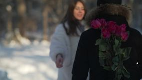 Young unrecognizable man holding flowers behind and waiting for his girlfriend stock video footage