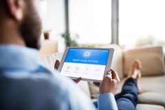 A man holding a tablet with smart home screen. An unrecognizable man holding a tablet with smart home control system stock photography