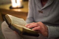 Unrecognizable man at home reading Bible, burning candles behind Royalty Free Stock Images