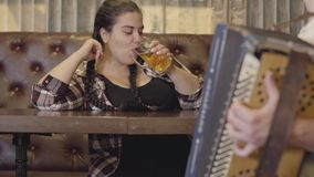 Unrecognizable man playing the accordion while attractive plump woman drinking beer and sending him air kiss. Concept of. Unrecognizable man playing the stock video