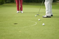 Unrecognizable man playing golf putting on green stock photos