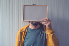 Unrecognizable man posing with blank picture frame over his face Stock Images