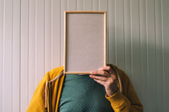 Unrecognizable man posing with blank picture frame over his face Royalty Free Stock Images