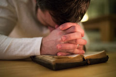 Unrecognizable man praying, kneeling on the floor, hands on Bibl Royalty Free Stock Photography