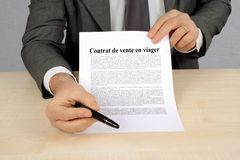 Life annuity contract written in French. Unrecognizable man presenting a life annuity sale contract written in French stock illustration