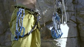 Unrecognizable man rock climber getting ready for outdoors climbing on cliff, and attaching quickdraws to the harness. Unrecognizable man rock climber getting stock footage