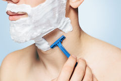 Unrecognizable man is shaving with razor Royalty Free Stock Image