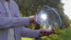 Unrecognizable man shows conceptual hologram with text Satellite navigation. Farmer on the background of the apple orchard in casual clothes with the stock footage
