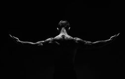 Unrecognizable man shows strong neck muscles closeup. Unrecognizable man bodybuilder shows strong hands and neck muscles, athletic trapezius. Black and white stock photo