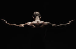 Unrecognizable man shows strong neck muscles closeup. Unrecognizable man bodybuilder shows strong hands and neck muscles, athletic trapezius. Low key, studio royalty free stock photo