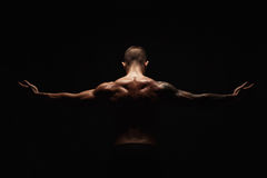 Unrecognizable man shows strong neck muscles closeup. Unrecognizable man bodybuilder shows strong hands and neck muscles, athletic trapezius. Low key, studio stock images
