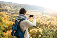 Unrecognizable man with smart phone against colorful autumn fore Royalty Free Stock Photo