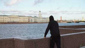 Unrecognizable man staying on city embankment. At winter sunny day stock footage